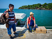 """13 FEBRUARY 2019 - SIHANOUKVILLE, CAMBODIA: Chinese tourists in Sihanoukville wait for a high speed ferry to take them to a nearby island. There are about 80 Chinese casinos and resort hotels open in Sihanoukville and dozens more under construction. The casinos are changing the city, once a sleepy port on Southeast Asia's """"backpacker trail"""" into a booming city. The change is coming with a cost though. Many Cambodian residents of Sihanoukville  have lost their homes to make way for the casinos and the jobs are going to Chinese workers, brought in to build casinos and work in the casinos.      PHOTO BY JACK KURTZ"""