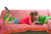 A teen studies on a couch in her room with a laptop