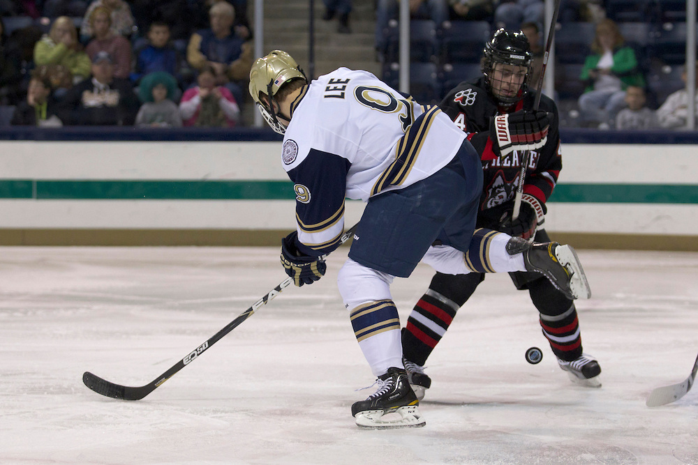 Notre Dame center Anders Lee (#9) and Northeastern defenseman Dan Cornell (#4) battle for loose puck in second period action during NCAA hockey game between Notre Dame and Northeastern.  The Northeastern Huskies defeated the Notre Dame Fighting Irish 9-2 in game at the Compton Family Ice Arena in South Bend, Indiana.