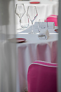 Modern restaurant and winery in white and pink colors with clean glasses on tables, France.