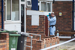 28/05/2016. London, UK. A police forensic investigator photographs a front door on Payne Street in Deptford, south London, where a 16-year-old boy was stabbed repeatedly. The victim's condition is said to be 'critical', and a police cordon remains in place as investigations continue. Photo credit: Rob Pinney