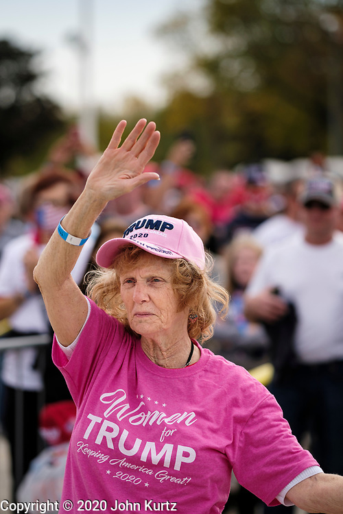 """14 OCTOBER 2020 - DES MOINES, IOWA: A woman raises her hand while she listens to people sing the Lee Greenwood song """"God Bless the USA"""" before a Donald Trump reelection rally. About10,000 people were expected at the Des Moines International Airport for a campaign rally supporting the reelection of President Donald Trump. Trump spoke at the rally, despite testing positive for COVID-19 less than three weeks ago. The rally did not meet the CDC guidelines for a safe gathering in the time of Coronavirus and violated Iowa's health emergency declarations barring gatherings of more than 25 people. This week Iowa exceeded 101,000 cases of COVID-19 and a surge in hospitalizations for COVID-19.         PHOTO BY JACK KURTZ"""