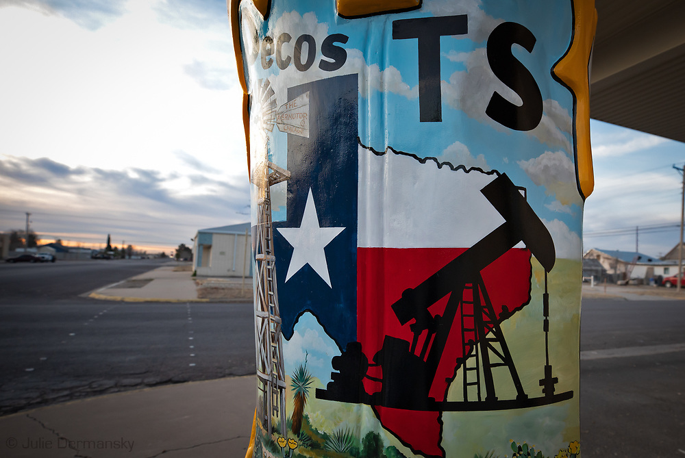 A oil and gas industry truck passing a giant boot in Pecos Texas in the Permian Basin.
