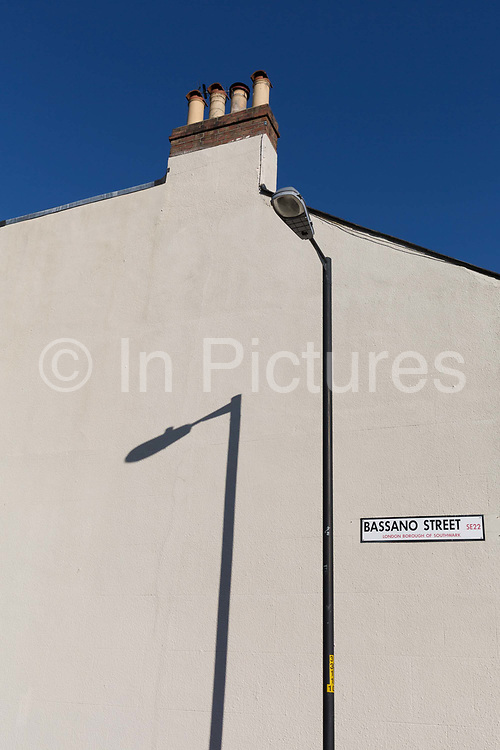 A shadow of a lamp post on the white outer wall of a house in East Dulwich,  on 15th March 2017, London borough of Southwark, England.