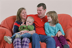 Family group sitting together on sofa smiling,