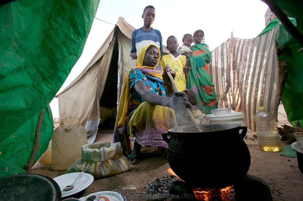 (MODEL RELEASED IMAGE) Squatting before the fire with her children, Sudanese Refugee D'jimia Ishakh Souleymane stirs a pot of aiysh, the thick porridge that this refugee family eats three times a day. Despite losing almost everything in their flight from militia attacks, D'jimia keeps her improvised household as orderly as possible. To cover the ground inside, the family hauled in clean sand from the dry riverbed. D'jimia and the children sleep on two blankets, which she constantly airs out and washes. Hungry Planet: What the World Eats (p. 64).