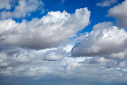 White fluffy cumulus clouds floating in blue sky above Shingle Street, Suffolk, England, UK