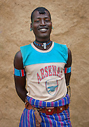 The football stars of tomorrow<br /> <br /> Thousands of Football shirts of Arsenal, Manchester, Chelsea, Milano, etc end up their carreer in... Ethiopia. Sold in the deep south, in the Omo Valley, those second hand clothes are bought by the local tribes. Most of them ignore the meaning of those shirts, and just buy them for the color, the logo, or the shape.<br /> No warrior will go out without his little pillow/seat.<br /> Some, like in Hamer tribe wear at the top of the head a clay helmet where they can put some ostrich feathers when they make a special action, like killing a wild animal, or...a man.<br /> Those tribes won't exist in few years as the ethiopian governement has launched a huge plan to develop the area.<br /> Soon, a highway coming from Mombassa - Nairobi will pass thru the villages to reach Addis Ababa.<br /> <br /> Photo shows: Bana tribe - Arsenal<br /> ©Eric Lafforgue/Exclusivepix Media