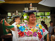 A Mexican waitress at a restaurant within Chichen Itza with a platter of drinks balance on her head. She is wearing a colorful, traditional blouse and dancing