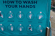 With a further 89 UK covid victims in the last 24hrs, bringing the total victims to 43,995 during the Coronavirus pandemic, pubs, restaurants and hairdressers will be able to reopen on 4th July, providing they adhere to COVID Secure guidelines. A Social Distance Ambassadors arm and gloved hands lean on a railing of a tent that demonstrates hand washing hygiene advice, on 2nd July 2020, in London, England.