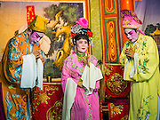 "06 DECEMBER 2015 - BANGKOK, THAILAND: A Chinese opera performance at the Ruby Goddess Shrine in the Dusit district of Bangkok. Chinese opera was once very popular in Thailand, where it is called ""Ngiew."" It is usually performed in the Teochew language. Millions of Chinese emigrated to Thailand (then Siam) in the 18th and 19th centuries and brought their culture with them. Recently the popularity of ngiew has faded as people turn to performances of opera on DVD or movies. There are about 30 Chinese opera troupes left in Bangkok and its environs. They are especially busy during Chinese New Year and Chinese holidays when they travel from Chinese temple to Chinese temple performing on stages they put up in streets near the temple, sometimes sleeping on hammocks they sling under their stage.     PHOTO BY JACK KURTZ"