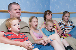 Family sitting on the sofa watching television together,