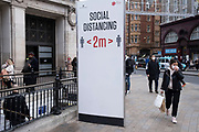 Socialdistancing sign as the national lockdown ends and the new three tier system of local coronavirus restrictions begins, shoppers head out to Oxford Street to catch up on shopping as non-essential shops are allowed to reopen on 2nd December 2020 in London, United Kingdom. Many shoppers wear face masks outside on the street as a precaution as there are so many people around.