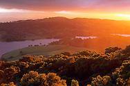 Sunset light on oak trees and hills above Anderson Lake, Santa Clara County, California
