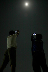 August 8, 2017 - Cibitung District, West Java, Indonesia - People try to capturing pictures of the partial lunar eclipse phenomenon by mobile phone camera at Cibitung District, West Java. The moon experienced a partial eclipse phenomenon with a duration of 5 hours 4.9 minutes.  (Credit Image: © Aditya Irawan/NurPhoto via ZUMA Press)