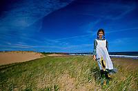 "Girl portraying ""Anne of Green Gables"" on dunes near Park Corner, Prince Edward Island, Canada"