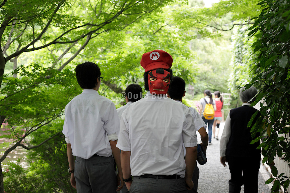 boy walking with a mask on the back of his head Japan