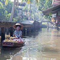 A woman rowing her boat at Damnoen Saduak canal.