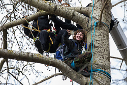 Steeple Claydon, UK. 24 February, 2021. An anti-HS2 activist takes a selfie as Thames Valley Police officers acting on behalf of HS2 Ltd use a cherry picker to evict her from ancient woodland known as Poors Piece. Thames Valley Police stepped in to replace National Eviction Team bailiffs. The activists created the Poors Piece Conservation Project in the woodland in spring 2020 after having been invited to stay on the land by its owner, farmer Clive Higgins.