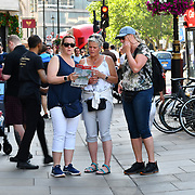 Tourists looking at a map at Trafalgar Square, on 27 June 2019, London, UK