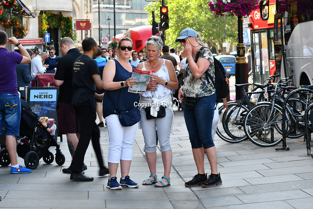 Tourists looking at a map at Trafalgar Square, on 27 June 2019, London, UK