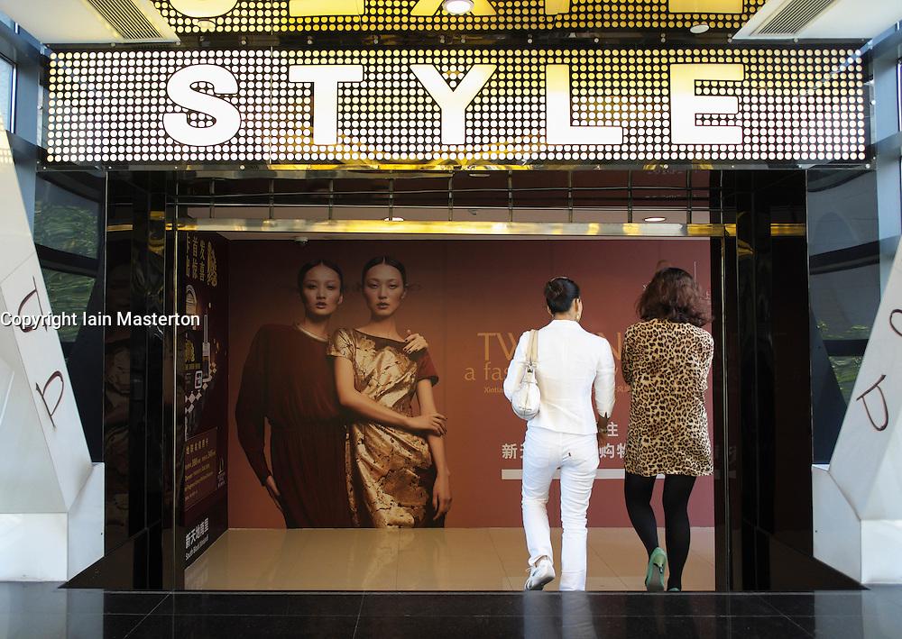 Two modern fashionable women walking in Xintiandi Style upmarket shopping mall in Shanghai