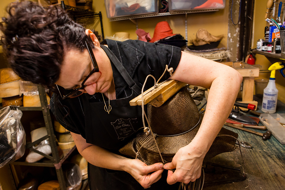 Tying a block called a tipper in place to hold the crease in the crown of a straw fedora.