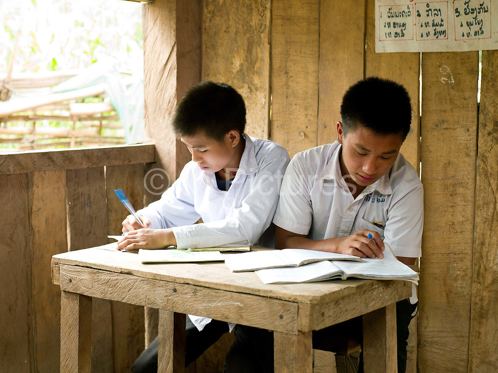 Phonekham (15) and Chom (15) studying at the lower secondary school in the Tai Lue village of Ban Hathin, Phongsaly province, Lao PDR. The remote and roadless village of Ban Hathin is situated along the Nam Ou river (a tributary of the Mekong) and will be relocated due to the construction of the Nam Ou Cascade Hydropower Project Dam 7. The Nam Ou river connects small riverside villages and provides the rural population with food for fishing. But this river and others like it, that are the lifeline of rural communities and local economies are being blocked, diverted and decimated by dams. The Lao government hopes to transform the country into 'the battery of Southeast Asia' by exporting the power to Thailand and Vietnam.