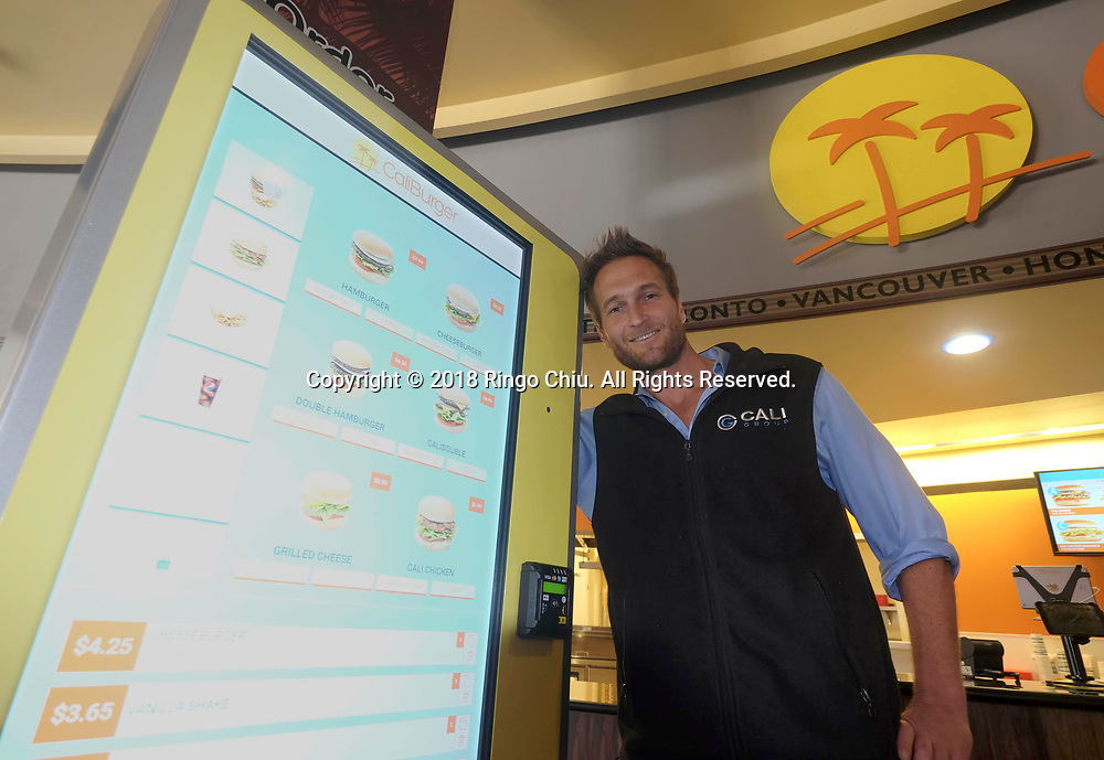John Miller, CaliBurger chairman, poses with a touch-screen kiosk for Flippy robotic arm at CaliBurger in Pasadena.  (Photo by Ringo Chiu)<br /> <br /> Usage Notes: This content is intended for editorial use only. For other uses, additional clearances may be required.