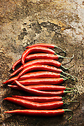 Spicy red chilli peppers arranged in a line on a rustic background.