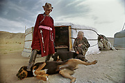 """Jolon holds his dog when visitors approach to his yurt, otherwis dogs might attack the traveller. To prevent a dog attack, local people signal themselves by shouting """"Hold your dog"""" when getting close to a yurt in Mongolia."""