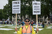 A campaigner holds two placards calling for the release of Wikileaks founder Julian Assange during a picnic in Parliament Square on the occasion of his 50th birthday on 3rd July 2021 in London, United Kingdom. An English court refused a request from the United States to extradite Assange earlier this year and campaigners have since urged President Biden to drop charges against him under the Espionage Act.
