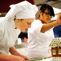 112712  Adron Gardner<br /> <br /> Susan Decker, left, looks over the finer details of a gingerbread house while Christine Martinez sprinkles powdered sugar the the roof in a University of New Mexico Gallup Center for Career and Technical Education class at Miyamura High School in Gallup Tuesday.  In past years, the gingerbread were raffled off but this year they will all be given to nursing and children's homes in McKinley County.