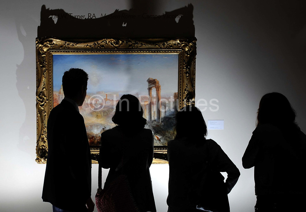A group of people look  at the painting, Modern Rome – Campo Vaccino by the British painter JM Turner at Sotheby's auction house. The painting sold for £29,721,150 at the auction at Sotheby's in central London.