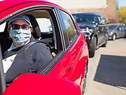 09 MAY 2020 - DES MOINES, IOWA: A person wearing a face mask waits to buy vegetables at a drive through farmers' market in Des Moines. The Governor allowed farmers' markets across the state to reopen last weekend, but limited them to selling just food stuffs. They are not allowed to have entertainment or sell non-food items. Most farmers' markets in Iowa are taking a wait and see approach to reopening. The Downtown Farmers Market in Des Moines announced they won't reopen until July. Three vendors set up their own drive through farmers' market in the parking lot of Des Moines theatre Saturday. Hundreds of people got in line to buy fresh produce and artisan cheese. More than 11,670 people have tested positive for COVID-19 in Iowa and more than 250 have died from the disease.          PHOTO BY JACK KURTZ
