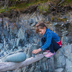 A young girl balances rocks on a driftwood log in a cove in Quoddy Head State Park in Lubec, Maine.
