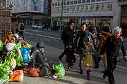 As passers-by walk by, a homeless man sits with all his worldly possessions on Piccadilly in central London. Two children accompanied by adults who walk past the vagrant who sits forlornly on the pavement, surrounded by his worldly good - plastic bags attached to an old bike. We see a scene of poverty and privilege - of wealth versus hopelessness - on this prestgious London street where money speaks volumes for those with successful lives.