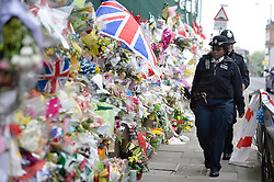 © London News Pictures. 31/05/2013. Woolwich, UK. POlice officers walk past flowers at the scene where Drummer Lee Rigby was killed in Woolwich, South East London. Photo credit: Ben Cawthra/LNP