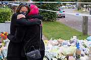 Two days after the killing of the Conservative member of parliament for Southend West, Sir David Amess MP, young women stand in front of floral tributes left in Eastwood Road North, a short distance from Belfairs Methodist Church in Leigh-on-Sea, on 17th October 2021, in Leigh-on-Sea, Southend , Essex, England. Amess was conducting his weekly constituency surgery when attacked with a knife by Ali Harbi Ali.