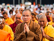 """22 FEBRUARY 2016 - KHLONG LUANG, PATHUM THANI, THAILAND:  Monks pray during Makha Bucha Day service at Wat Phra Dhammakaya.  Makha Bucha Day is a public holiday in Cambodia, Laos, Myanmar and Thailand. Many people go to the temple to perform merit-making activities on Makha Bucha Day, which marks four important events in Buddhism: 1,250 disciples came to see the Buddha without being summoned, all of them were Arhantas, Enlightened Ones, and all were ordained by the Buddha himself. The Buddha gave those Arhantas the principles of Buddhism, called """"The ovadhapatimokha"""". Those principles are:  1) To cease from all evil, 2) To do what is good, 3) To cleanse one's mind. The Buddha delivered an important sermon on that day which laid down the principles of the Buddhist teachings. In Thailand, this teaching has been dubbed the """"Heart of Buddhism."""" Wat Phra Dhammakaya is the center of the Dhammakaya Movement, a Buddhist sect founded in the 1970s and led by Phra Dhammachayo.     PHOTO BY JACK KURTZ"""