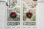 The wooden garden gate of a historic home decorated with a Christmas wreath on Lagare Street in Charleston, SC.
