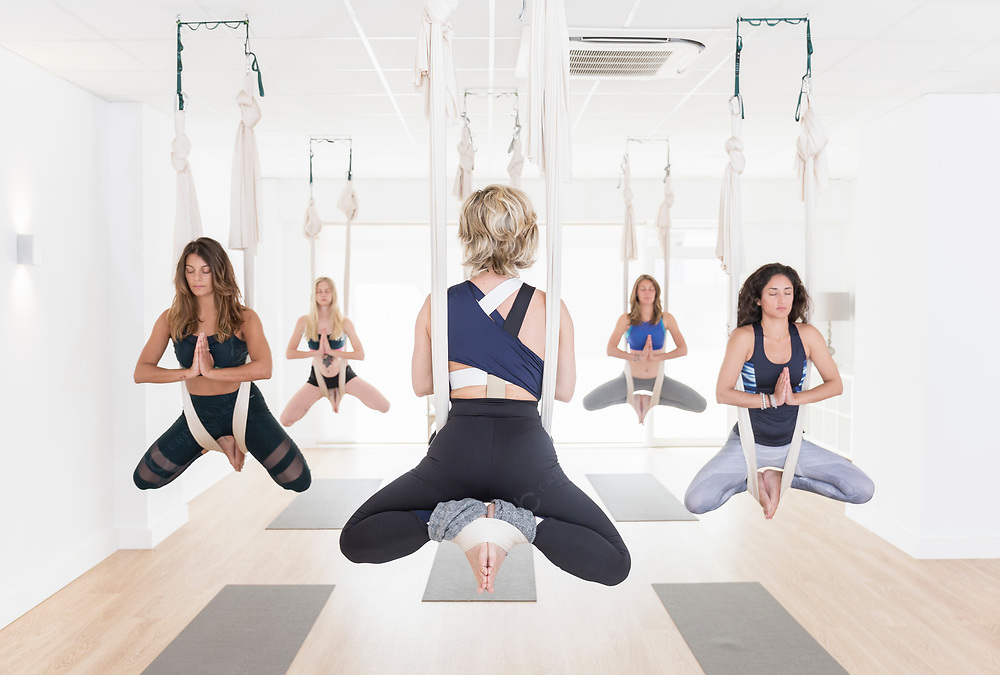A teacher is guiding her students during aerial yoga class