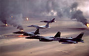 During Operation Desert Storm (1991) F-16A Fighting Falcon, F-15E Strike Eagle, and F-15C Eagle fighter jets fly over Kuwait's burning oil fields.