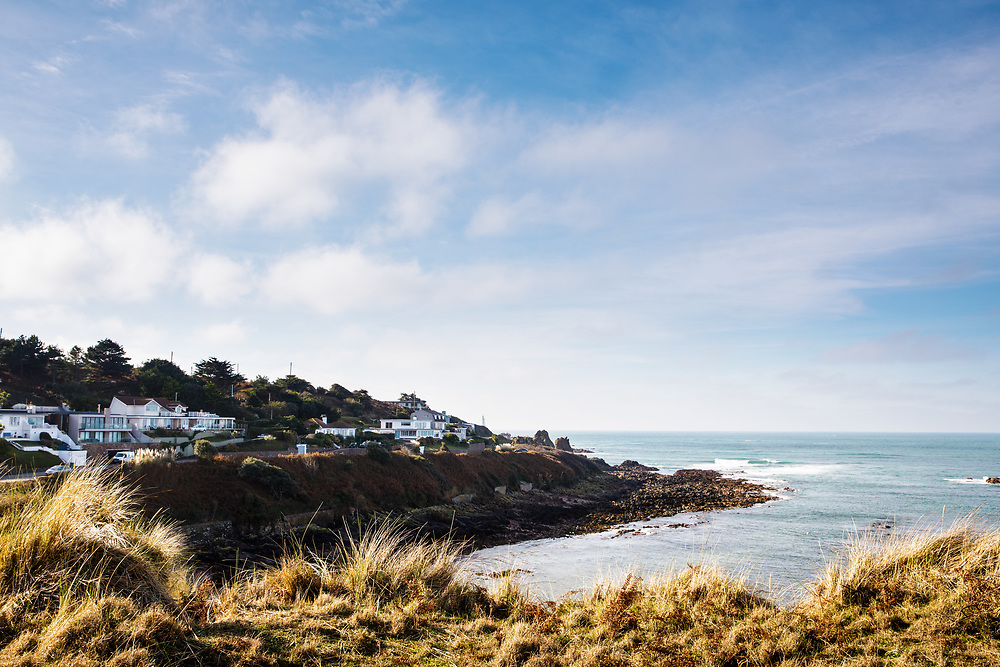 View across Petit Port beach from the cliff paths towards the  residential properties overlooking the bay in St Ouen, Jersey, CI
