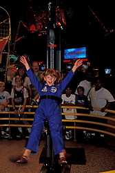 Child enjoying exhibit at Johnson Space Center Houston with onlooking crowd.