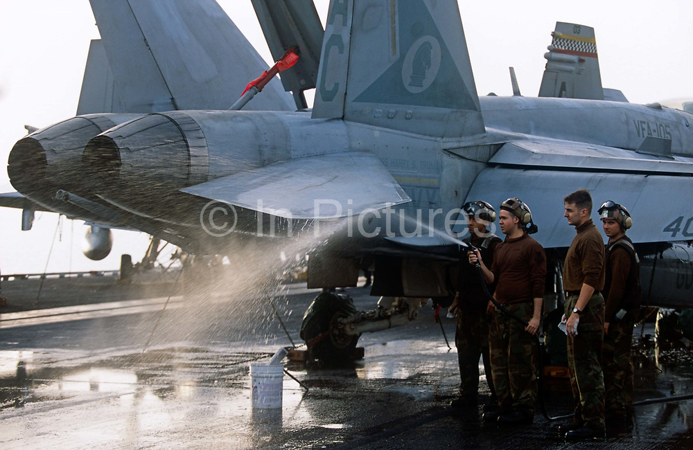 Brown-shirted plane captains, responsible for cleanliness and operating readiness of aircraft on deck, wash an F/A-18. Launched on 7 September 1996 and costing US$4.5 billion, the Truman (CVN-75) is the eighth Nimitz-class supercarrier of the United States Navy, named after the 33rd President of the United States, Harry S. Truman. The Truman is the largest of the US Navy's fleet of new generation carriers, a 97,000 ton floating city with a crew of 5,137, 650 are women.