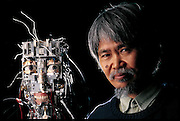 After he removes its skin, Fumio Hara gets the once-over from a face robot in the lab he co-directs with Hiroshi Kobayashi at the Science University of Tokyo, Japan. The first of several face robots made in his lab, it has a CCD camera in its left eye that sends images to neural-network software that recognizes faces and their expressions. Calling upon its repertoire of programmed reactions, it activates the motors and pulleys beneath its flexible skin to produce facial expressions of its own. The project is relatively unusual in its focus, many researchers believe that making robots walk and manipulate objects is so difficult that facial expressions are not yet worth working on. Hara disagrees, arguing that robots with animated faces will communicate with humans much more easily. From the book Robo sapiens: Evolution of a New Species, page 74-75.