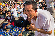 "23 MARCH 2013 - NAKHON CHAI SI, NAKHON PATHOM, THAILAND:  A man channeling a wild animal stalks the stage at the Wat Bang Phra tattoo festival. Wat Bang Phra is the best known ""Sak Yant"" tattoo temple in Thailand. It's located in Nakhon Pathom province, about 40 miles from Bangkok. The tattoos are given with hollow stainless steel needles and are thought to possess magical powers of protection. The tattoos, which are given by Buddhist monks, are popular with soldiers, policeman and gangsters, people who generally live in harm's way. The tattoo must be activated to remain powerful and the annual Wai Khru Ceremony (tattoo festival) at the temple draws thousands of devotees who come to the temple to activate or renew the tattoos. People go into trance like states and then assume the personality of their tattoo, so people with tiger tattoos assume the personality of a tiger, people with monkey tattoos take on the personality of a monkey and so on. In recent years the tattoo festival has become popular with tourists who make the trip to Nakorn Pathom province to see a side of ""exotic"" Thailand. The 2013 tattoo festival was on March 23.   PHOTO BY JACK KURTZ"