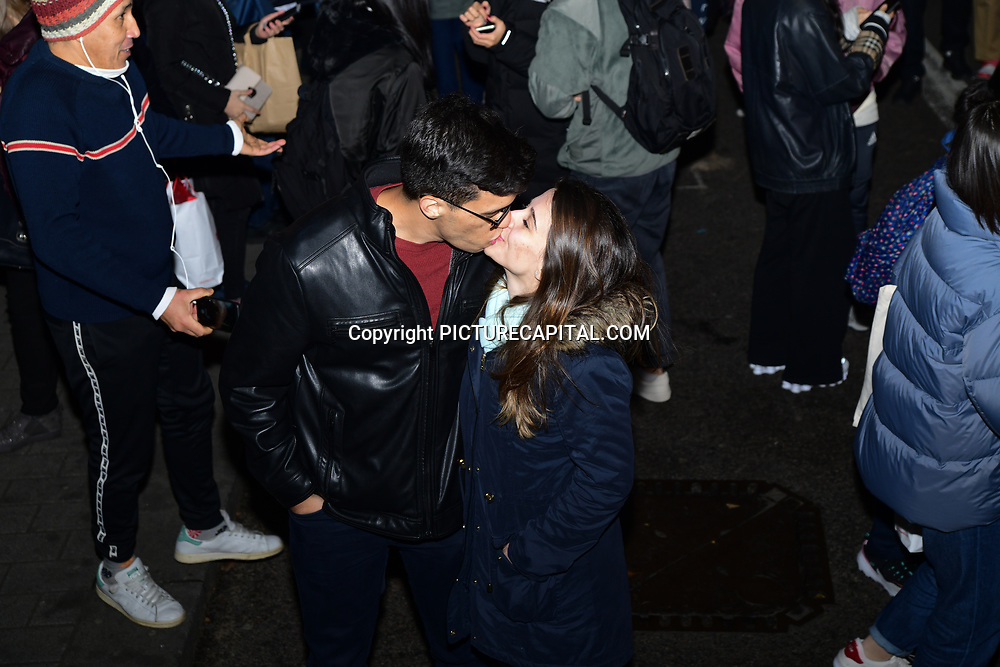 A couple kissing at Regent Street Christmas Lights switch-on celebrate its 200th anniversary on 14 November 2019, London, UK.
