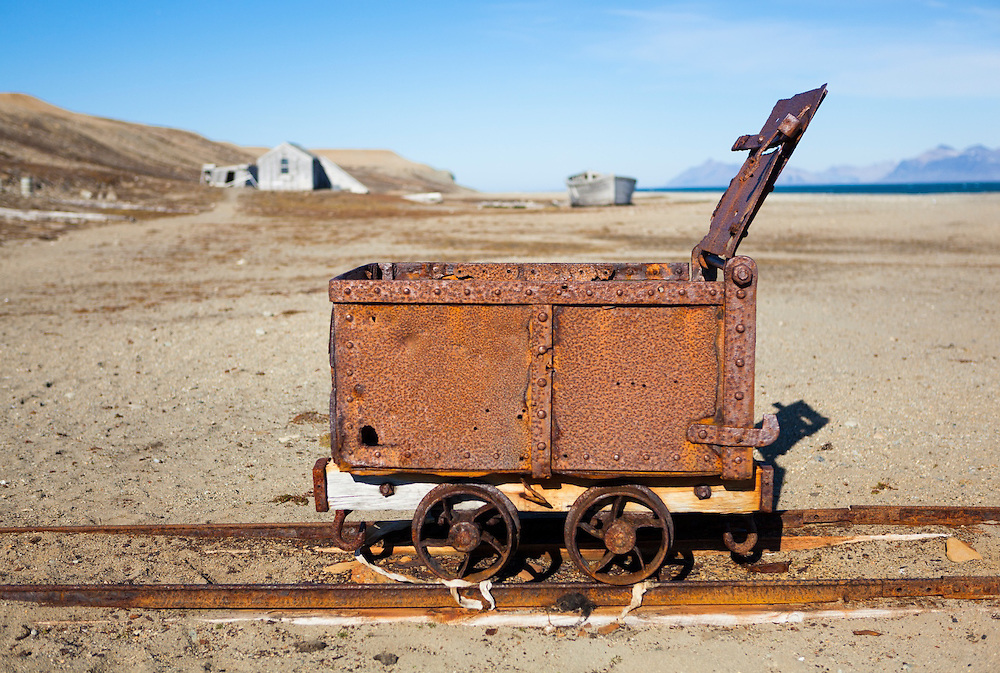 Remains of a narrow gauge railway with a rusted carriage on the beach at Calypsobyen, Svalbard, site of a coal mining operation erected by the British Northern Exploration Company in the early 1900s. Structures and a barge are visible in the distance.